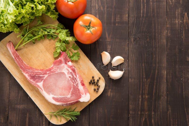 Verse Ruwe Varkenskoteletten en groente op houten achtergrond stock foto