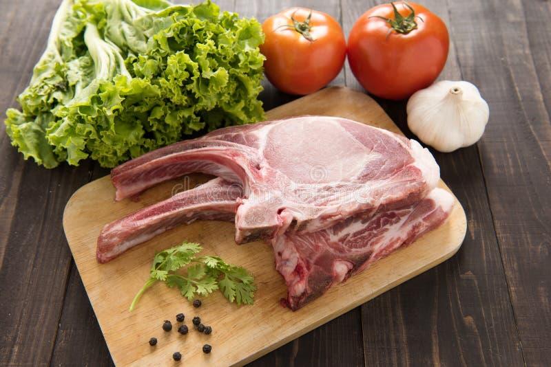Verse Ruwe Varkenskoteletten en groente op houten achtergrond royalty-vrije stock afbeeldingen