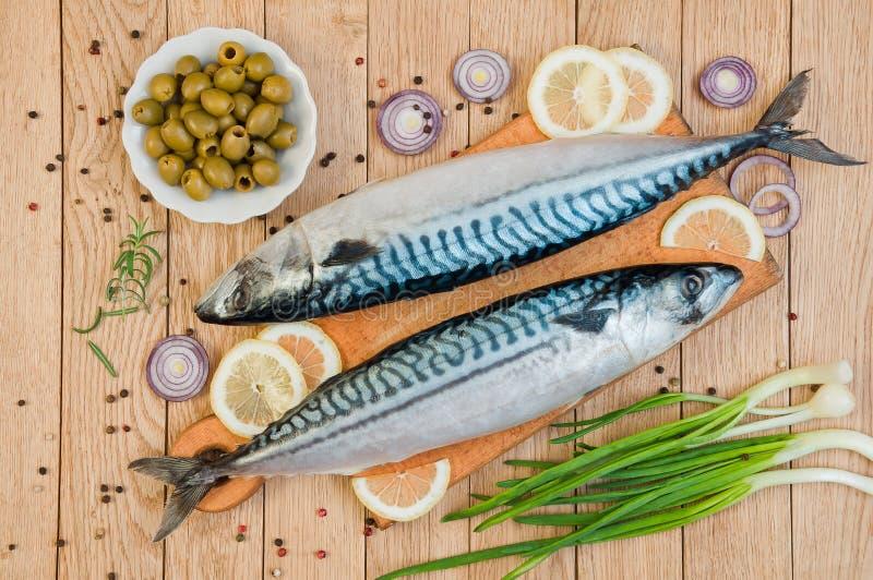 Verse ruwe vissenmakreel en ingrediënten voor het koken op houten stock afbeeldingen