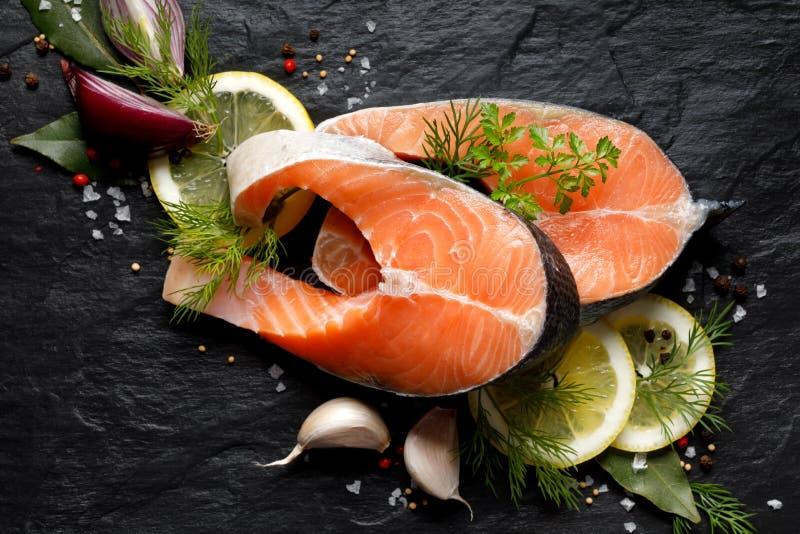 Verse, ruwe zalmlapjes vlees met de toevoeging van plakken van citroen, knoflook, ui, kruiden en kruiden op een zwarte steenachte stock foto