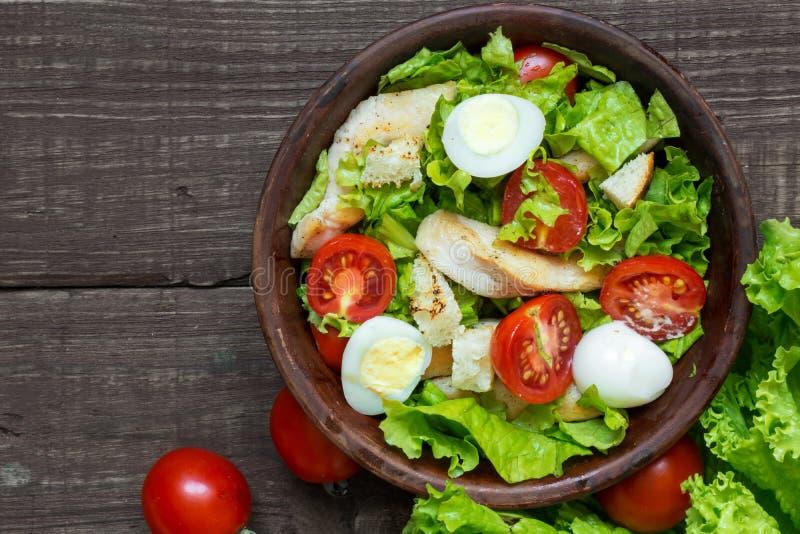 Verse salade caesar met kip, kwartelseieren, tomaten en sla in een kom royalty-vrije stock afbeeldingen