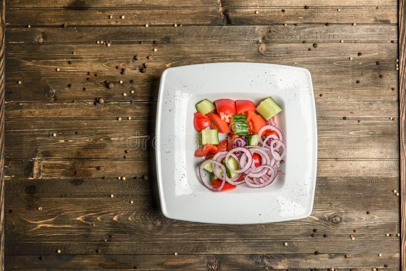 Verse salade en groenten in witte plaat op houten hoogste mening als achtergrond royalty-vrije stock afbeeldingen