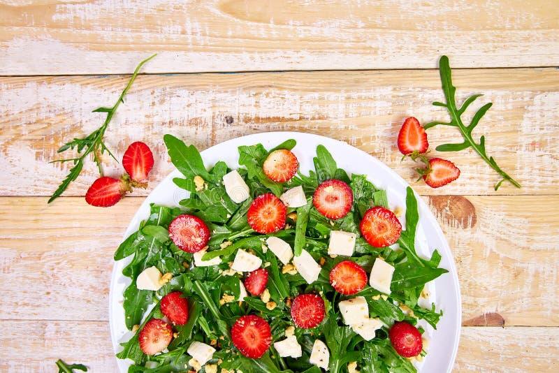 Verse salade met arugula, aardbeien, feta-kaas en noten stock afbeelding