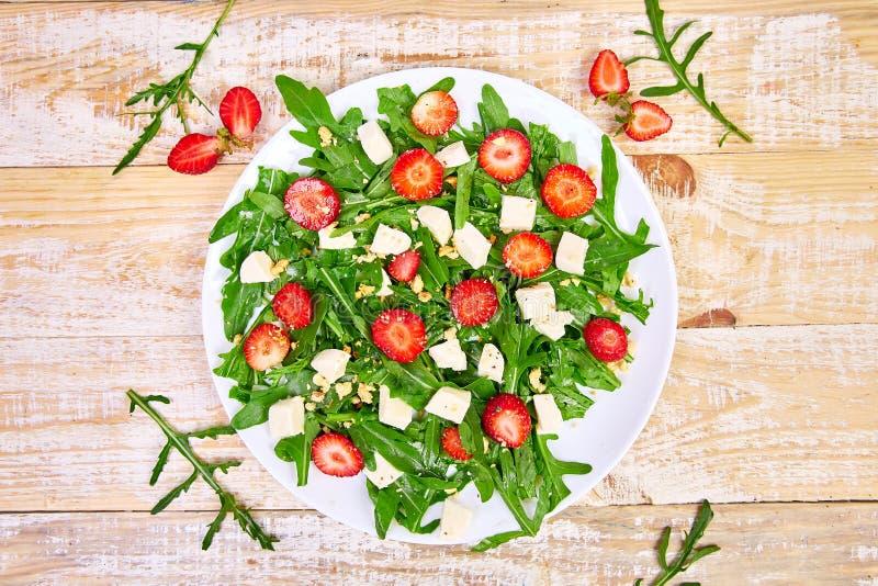 Verse salade met arugula, aardbeien, feta-kaas en noten stock foto