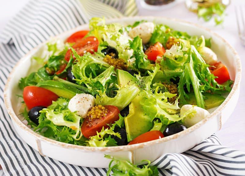 Verse salade met avocado, tomaat, olijven en mozarella in een kom royalty-vrije stock foto
