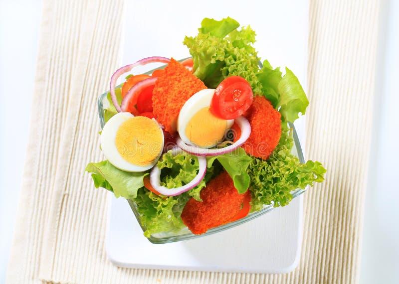 Verse salade met gebraden gepaneerd kaas en ei stock foto