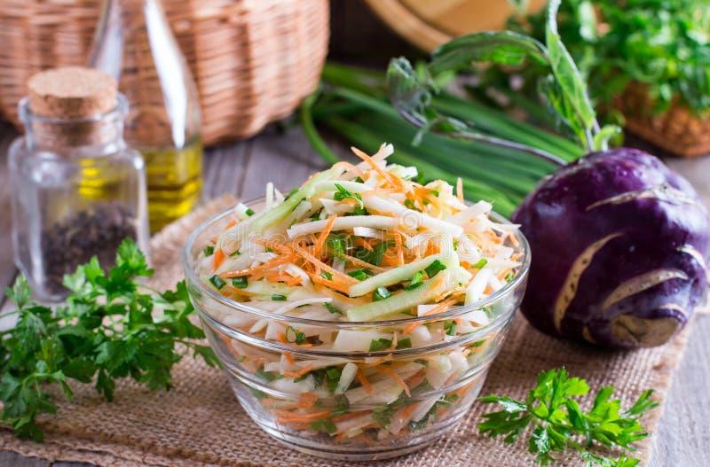 Verse salade met koolraap, komkommer, wortelen en kruiden in een kom Vegetarisch voedsel Smakelijke en gezonde schotel Het gezond stock afbeelding