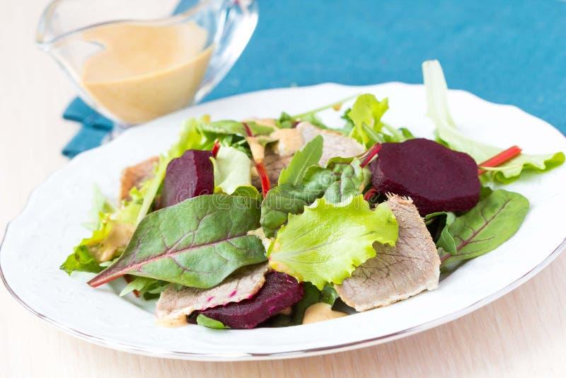 Verse salade met slabladeren, gekookt rundvlees, biet, mosterd stock foto