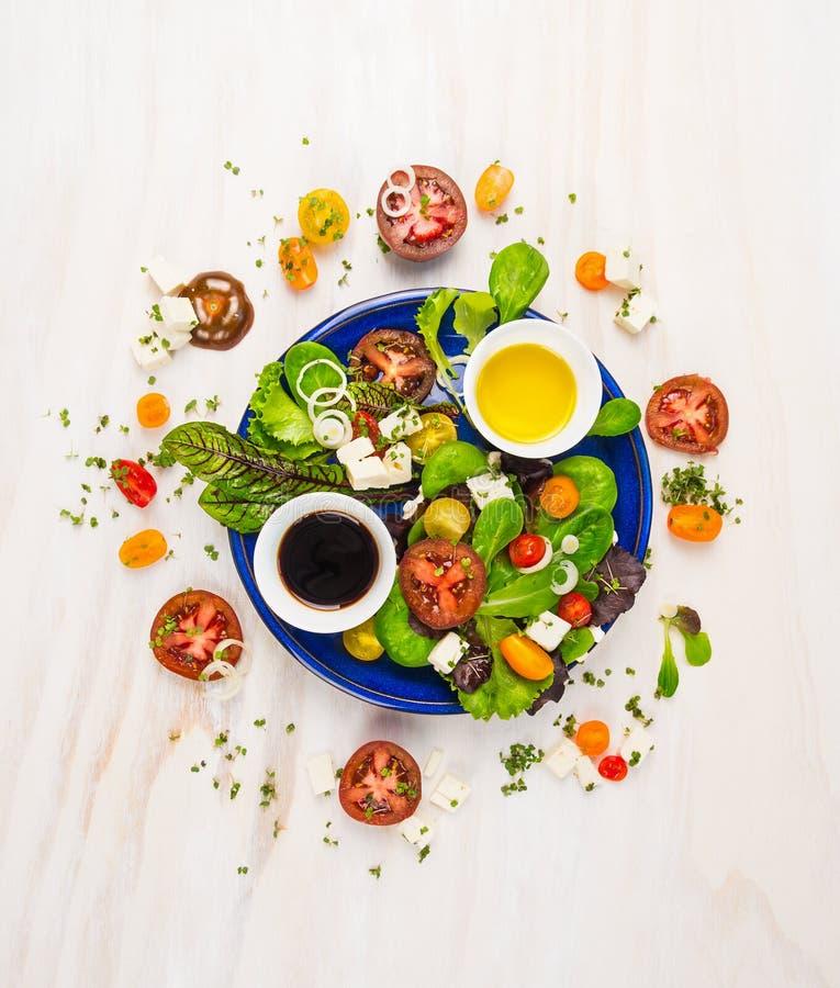 Verse salade met tomaten, feta-kaas, balsemieke azijn en olie in blauwe plaat op witte houten achtergrond stock afbeelding