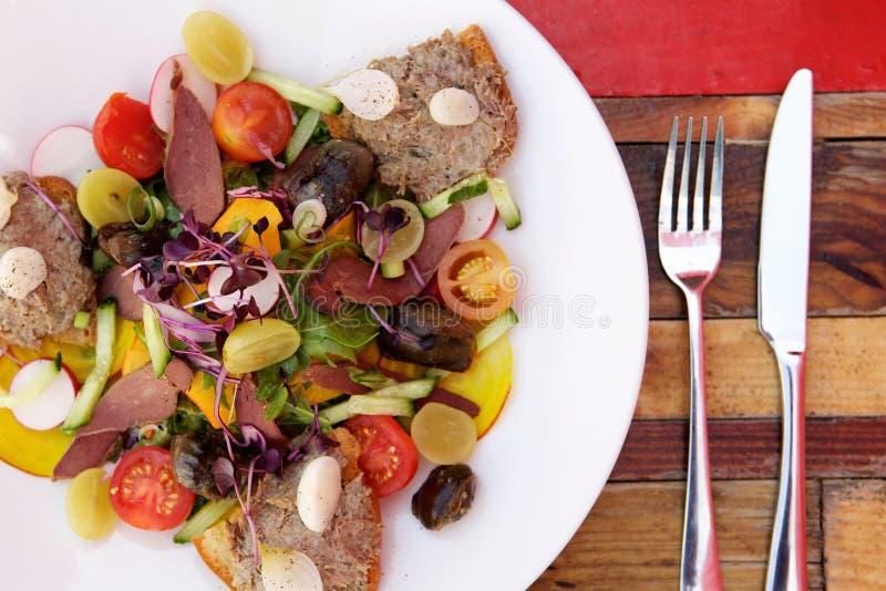 Verse salade op een plaat met geroosterde brood en vleespastei royalty-vrije stock afbeelding