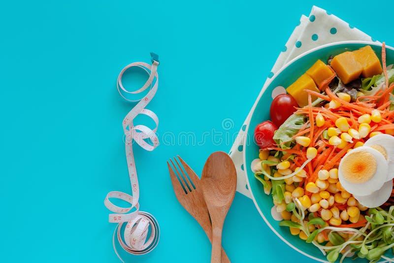 Verse saladegroente met gekookt kippenei, die band, houten lepel en vork op blauwe achtergrond meten royalty-vrije stock afbeelding