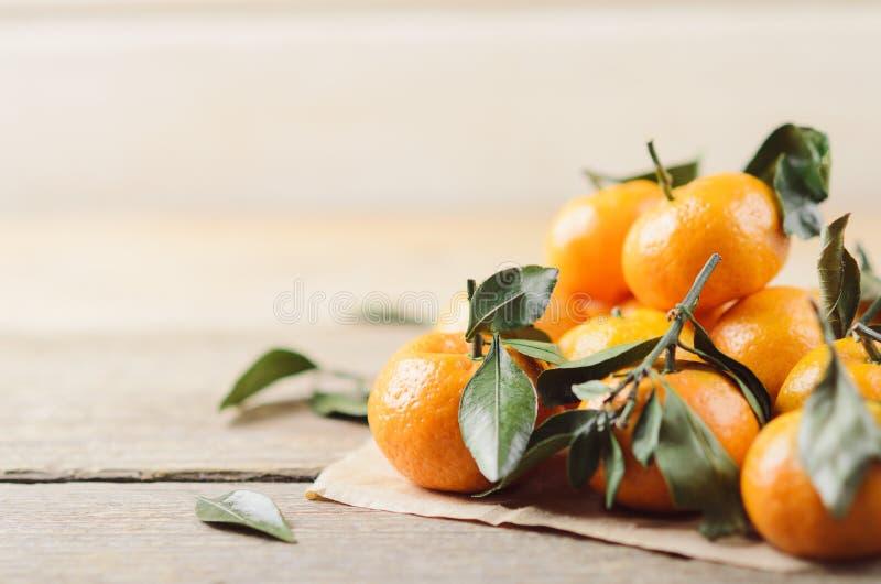 Verse sappige kleine mandarijnen met groene bladeren in een hoop op wit houten document als achtergrond en ambacht Nuttige citrus stock afbeeldingen