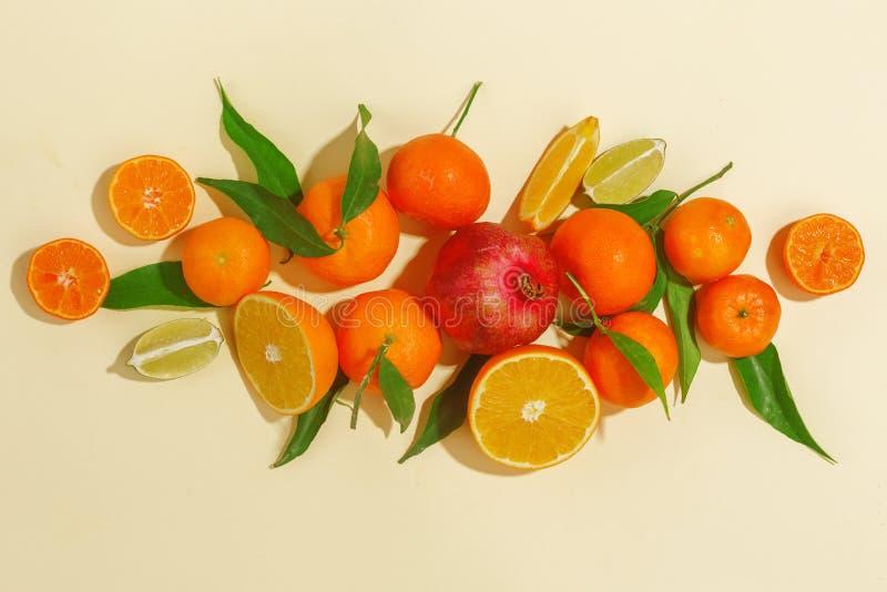 Verse sappige mandarijnen, granaatappels en gesneden vruchten op een gele achtergrond De zomerstemming, gezond voedsel Hoogste me stock foto