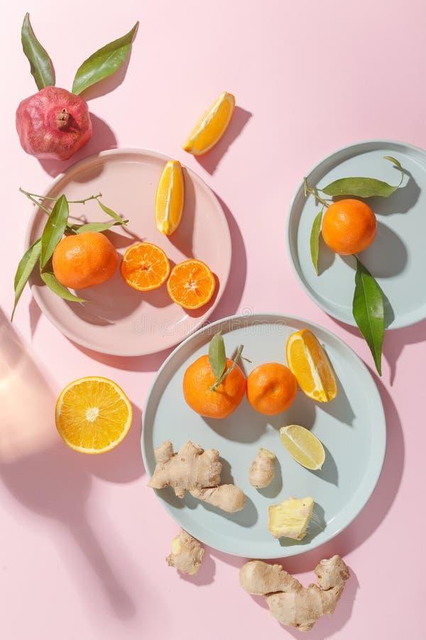 Verse sappige mandarijnen, granaatappels en gesneden vruchten op gekleurde platen op een roze achtergrond De zomerstemming, gezon stock foto's