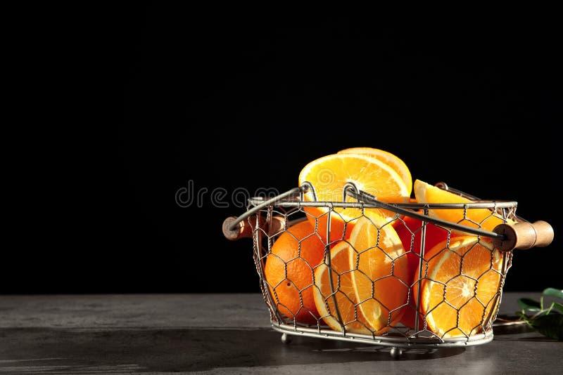 Verse sappige sinaasappelen in mand op grijze lijst royalty-vrije stock afbeelding