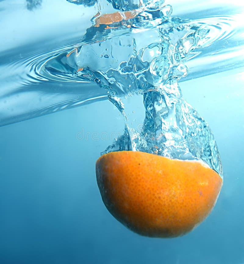 Verse sinaasappel in blauw, duidelijk water stock afbeeldingen