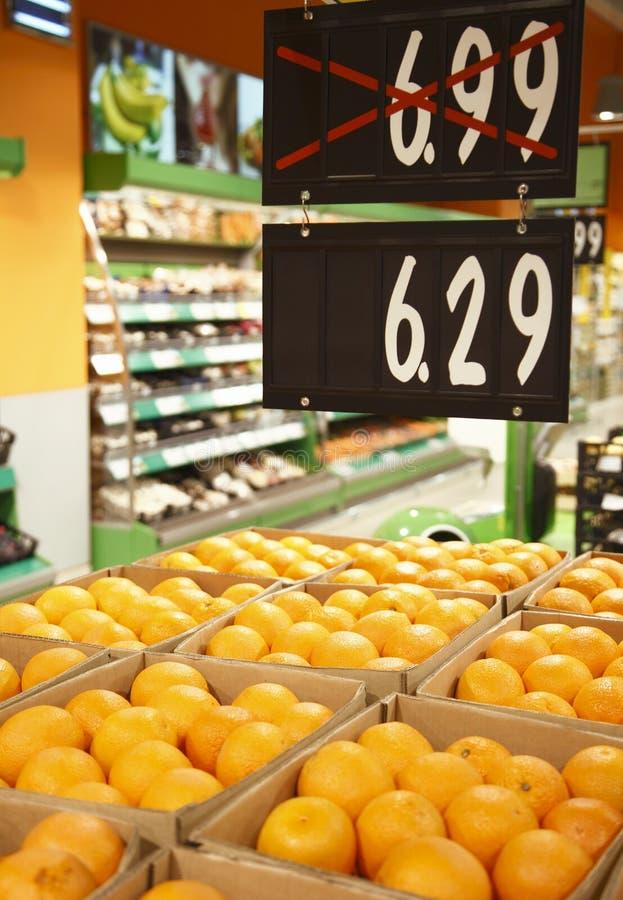 Verse sinaasappelen in kruidenierswinkel met kortingen stock fotografie