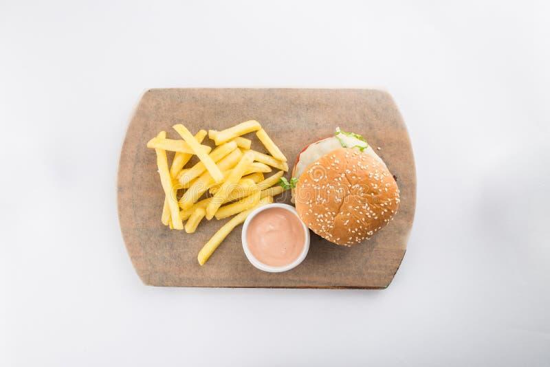Verse smakelijke die rundvleeshamburger met kaas en frieten op witte achtergrond worden ge?soleerd stock foto's