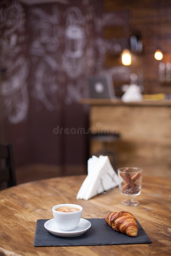 Verse smakelijke espressokop van hete koffie op houten naast een heerlijk croissant stock foto