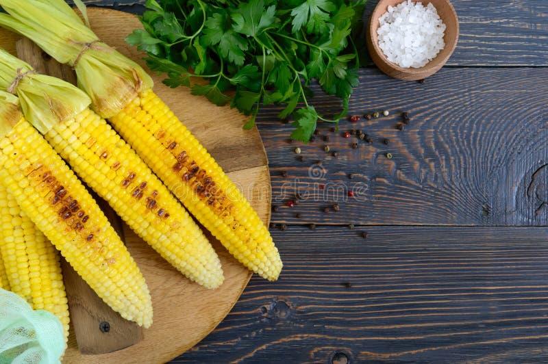 Verse smakelijke geroosterde suikermaïs met boter, overzees zout en koriander op een houten lijst royalty-vrije stock afbeelding