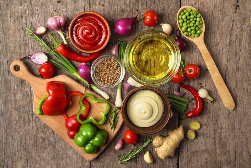 Verse smakelijke ingrediënten voor het gezonde koken of salade met rode saus, mayonaise en boter met kruiden op een plattelander royalty-vrije stock afbeelding
