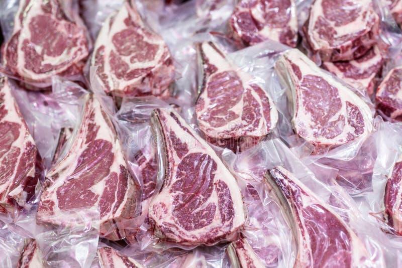 Verse smakelijke ruwe die rundvleeslapjes vlees met been in vacuümplastiek wordt verpakt stock afbeeldingen