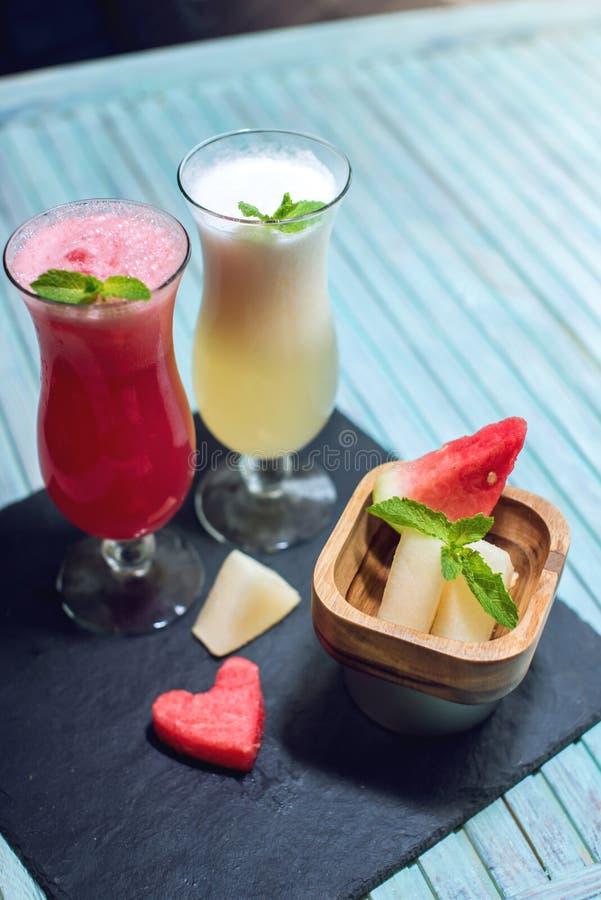 Verse smoothie in een glas met gesneden stukken van watermeloen en meloen met munt op blauwe achtergrond De zomer koele dranken stock foto's