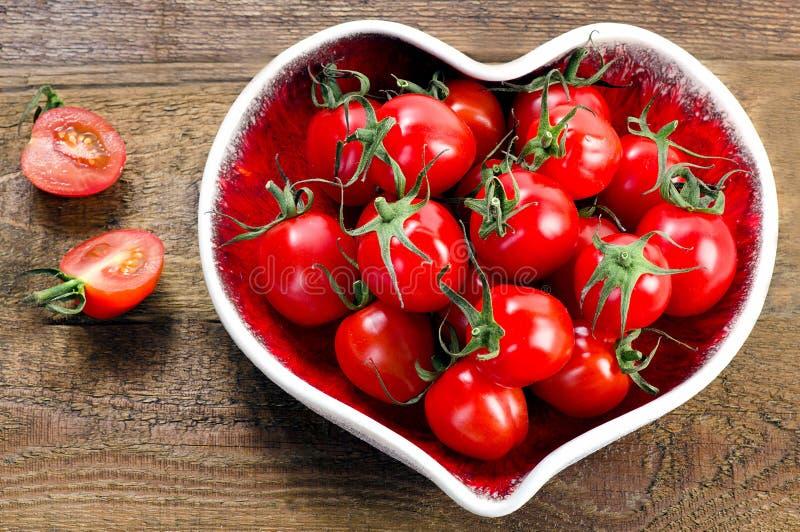 Verse tomaten in een hart gevormde plaat Gezond voedsel royalty-vrije stock afbeeldingen