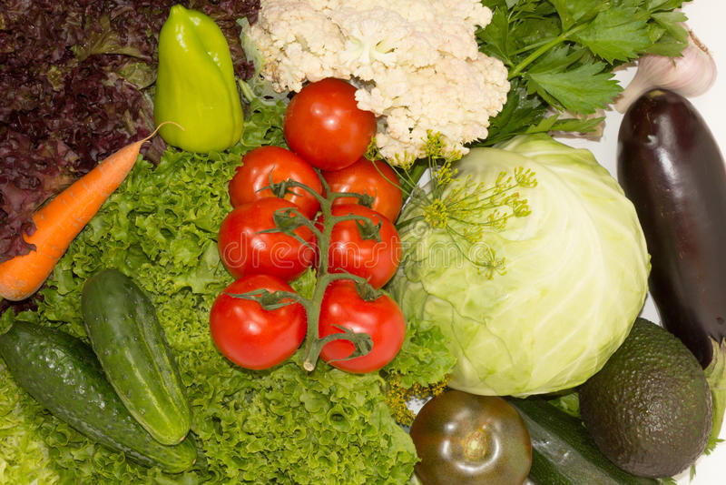 Verse tomaten en Spaanse pepers op de groene koolzaadachtergrond royalty-vrije stock afbeelding