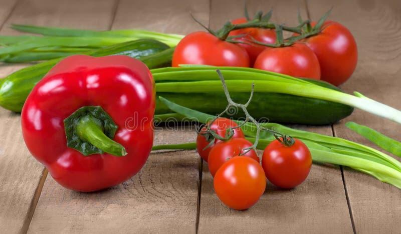 Verse tomaten, komkommers en uien op een houten raad royalty-vrije stock fotografie