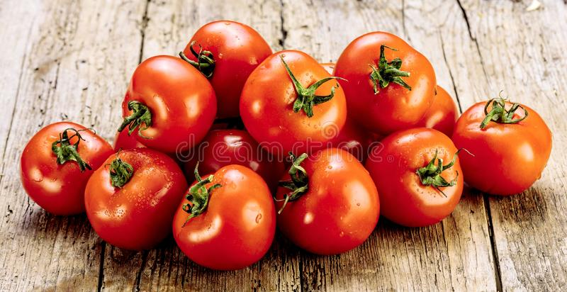 Verse tomaten op een oude houten lijst Het kweken van vruchten en groenten Gezond voedsel Ruw vegetarisch voedsel Verkoop van tom stock foto
