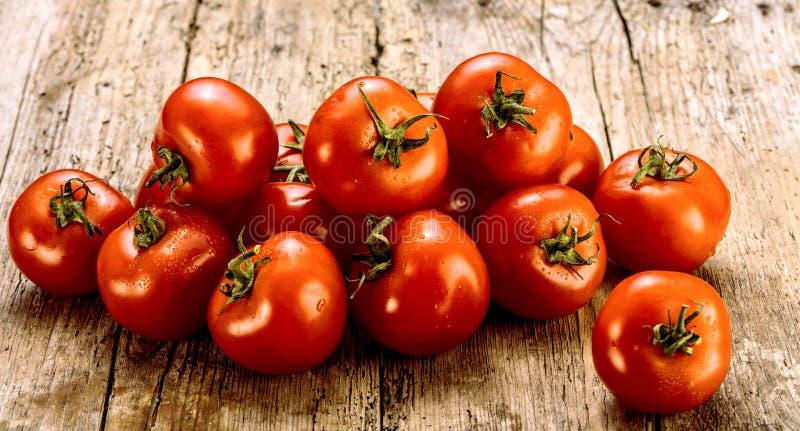 Verse tomaten op een oude houten lijst Het kweken van vruchten en groenten Gezond voedsel Ruw vegetarisch voedsel Verkoop van tom stock fotografie