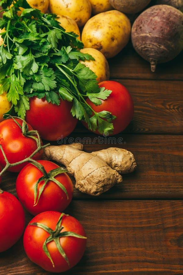 Verse tomaten, peterselie, aardappels en bieten op rustieke houten achtergrond Concept van het landbouwers` s het gezonde voedsel royalty-vrije stock foto