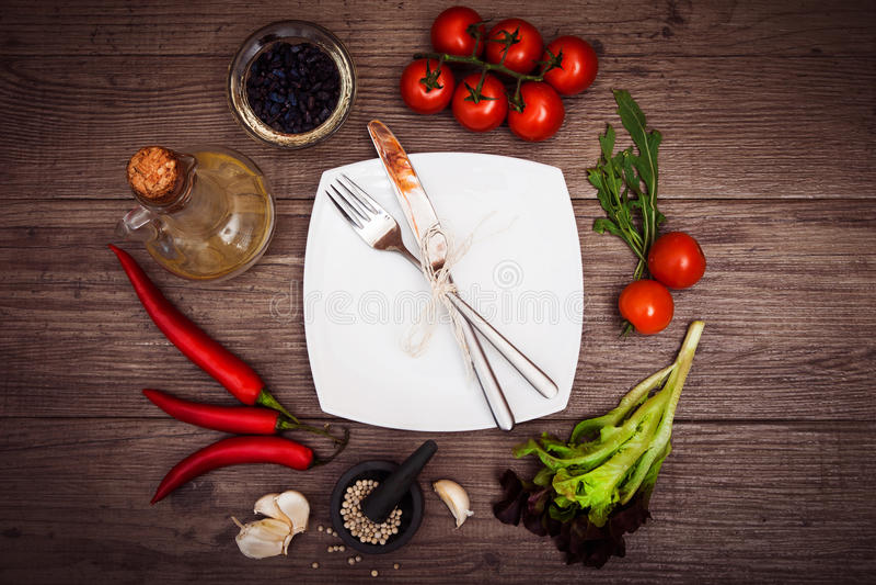 Verse tomaten, Spaanse peperpeper en andere kruiden en kruiden rond moderne witte vierkante plaat in het centrum van houten lijst royalty-vrije stock afbeelding
