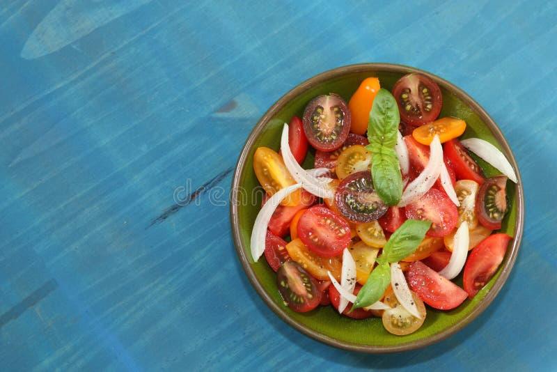 Verse tomatensalade met ui en basilicum stock afbeeldingen