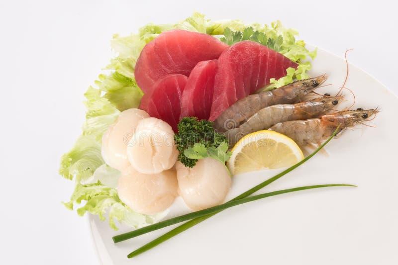 Verse tonijnvissen, garnalen en kammosselshell in een plaat stock fotografie