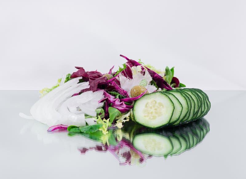 Verse tropische plantaardige salade - Gesneden komkommer, gehakte rode kool, olijven, spinazie en gehakte uien stock fotografie