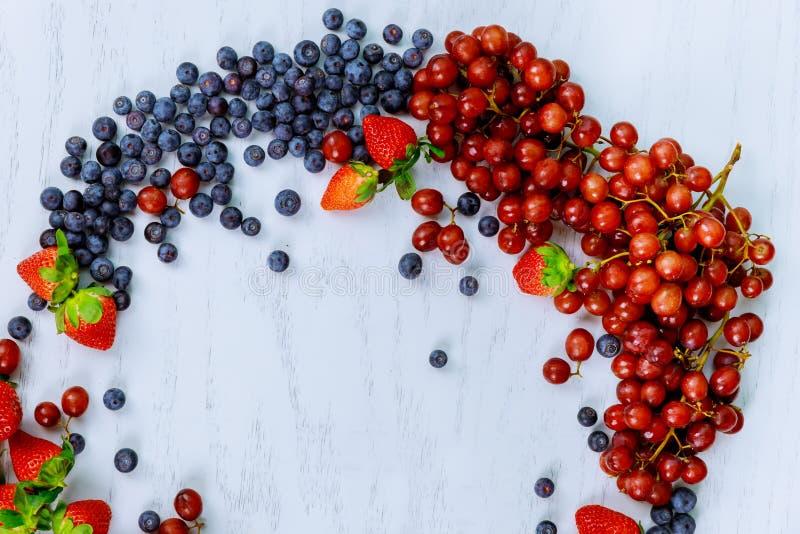Verse tuinbessen en druiven op een witte houten horizontale lijst, stock afbeeldingen
