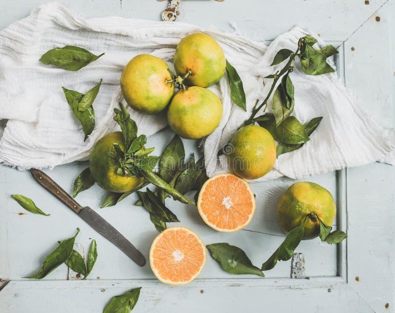 Verse Turkse mandarijnen met bladeren over blauwe rustieke houten achtergrond stock afbeelding