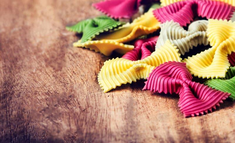 Verse Verse Italiaanse Deegwaren op oude uitstekende houten lijst Ruwe dichte omhooggaand van Vlinderdas kleurrijke deegwaren Ruw royalty-vrije stock foto's