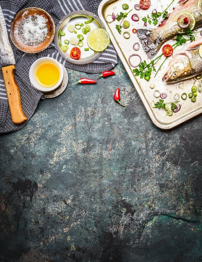 Verse vissen bij het koken van pan met ingrediënten, olie en kruiden op rustieke achtergrond, hoogste mening Gezond voedsel stock foto's