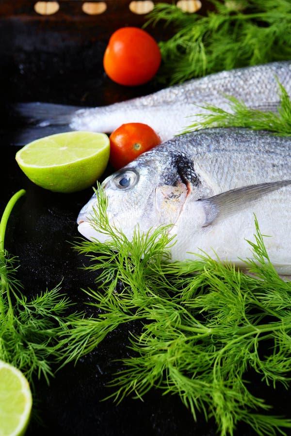 Verse vissen op een bakselblad en greens royalty-vrije stock foto's