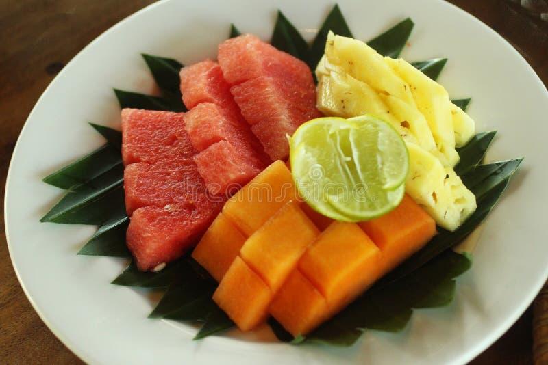 Verse vruchten op witte plaat met de natuurlijke regeling van het banaanblad Besnoeiings Gezonde vruchten, papaja, watermeloen, a stock foto's