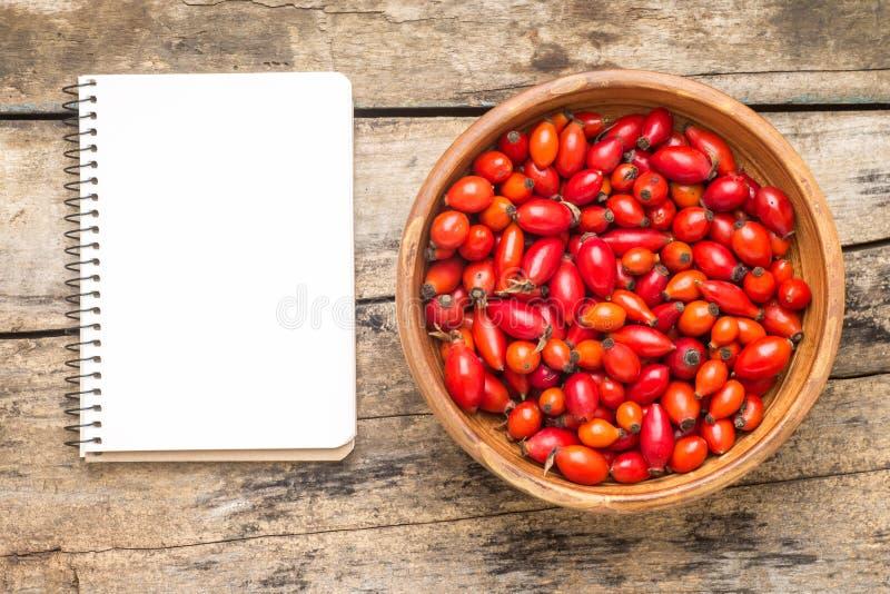 Verse wilde bessen met leeg receptenboek op houten achtergrond stock foto