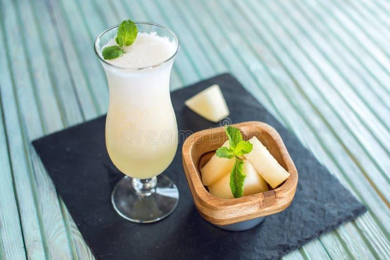 Verse witte smoothie in een glas met gesneden stukken van meloen en munt op een blauwe houten achtergrond De zomer koele dranken stock foto's