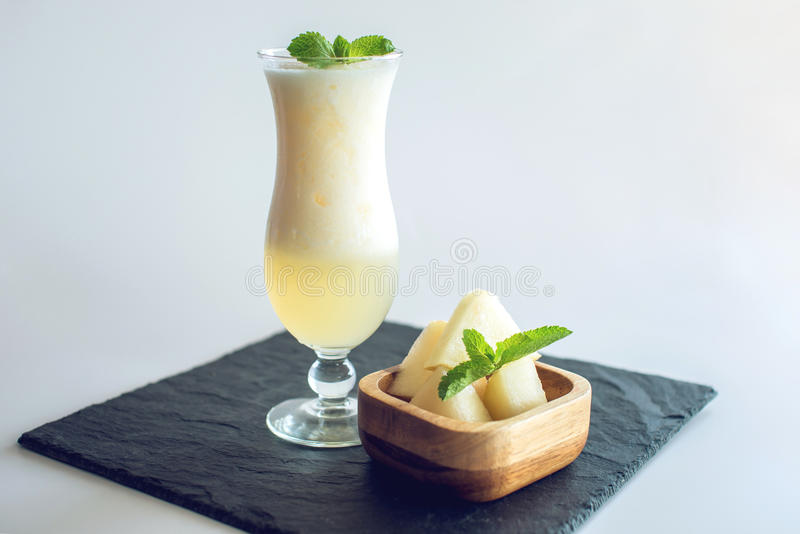 Verse witte smoothie in een glas met gesneden stukken van meloen en munt op wit isoleerde achtergrond De zomer koele dranken royalty-vrije stock foto's