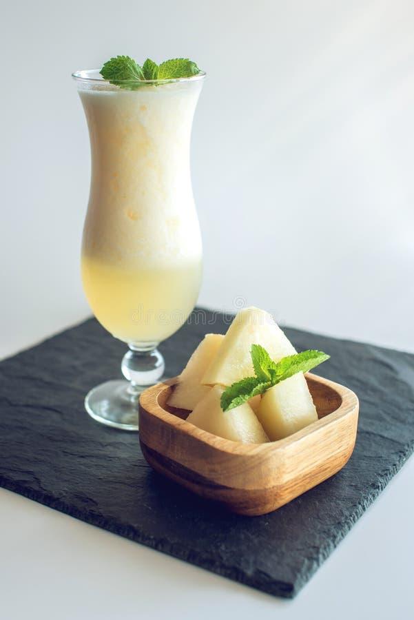 Verse witte smoothie in een glas met gesneden stukken van meloen en munt op wit isoleerde achtergrond De zomer koele dranken stock foto's