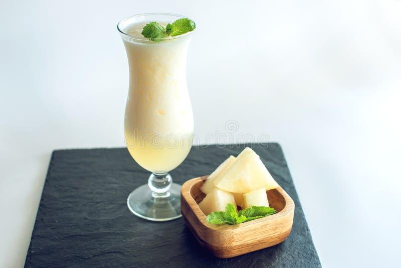 Verse witte smoothie in een glas met gesneden stukken van meloen en munt op wit isoleerde achtergrond De zomer koele dranken royalty-vrije stock fotografie