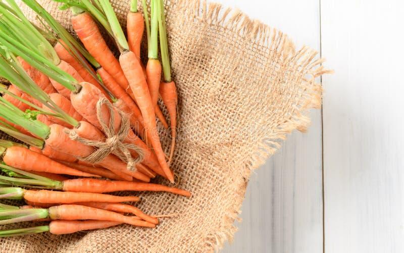 Verse wortel, babywortel op zak en wit hout royalty-vrije stock afbeeldingen