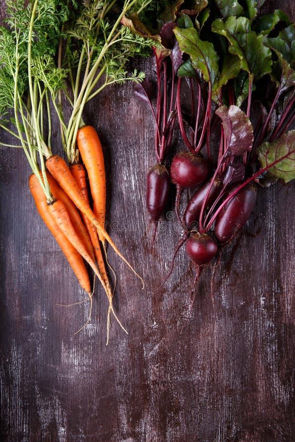 Verse wortelen en bieten met groene bladeren op donkere achtergrond stock foto's